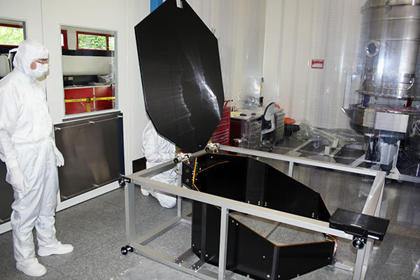 New clean room: in the foreground the telescope lid of eROSITA in the material lock, in the background the thermal vacuum chamber V and work table