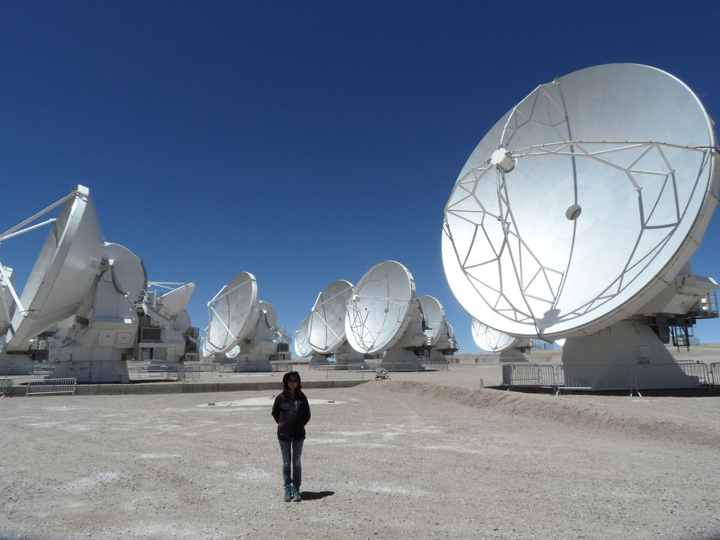 "Recent image of Paola Caselli at the site of the ALMA Observatory. The ""Atacama Large Millimeter/sub-millimeter Array"" is an interferometer of 66 high-precision radio telescopes in the Atacama desert in Northern Chile. The telescope array will observe at millimetre and sub-millimetre wavelengths to probe the very first stars and galaxies, and directly image exo-planets, possibly discovering the first traces of life."